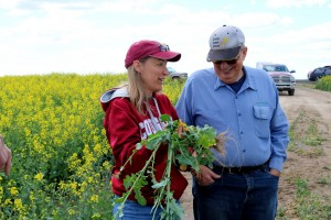 Karen Sowers holding a canola plant.