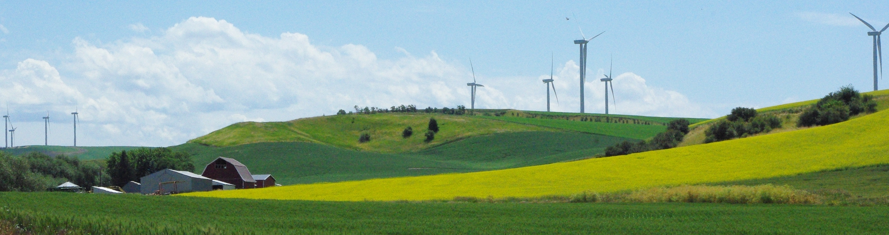 Landscape with a farmhouse, hills, and wind turbines.